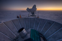 The sun sets behind BICEP2 (in the foreground) and the South Pole Telescope (in the background). (<i>Steffen Richter, Harvard University</i>)