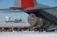 Liquid Helium for use in BICEP2 (in the background to the right), is being unloaded from a LC-130 aircraft at the Geographic South Pole. (<i>Steffen Richter, Harvard University</i>)